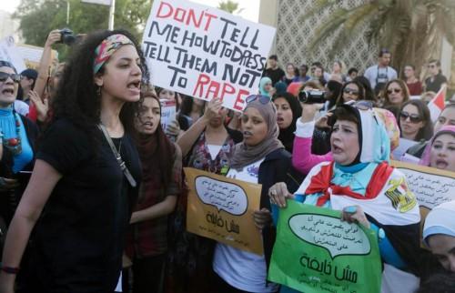 """Femme protestant contre le harcèlement sexuel en Egypte,  au Caire, Juin 2014.  Pancarte: """"Ne me dites pas comment m'habiller, dites-leur de ne pas violer."""""""